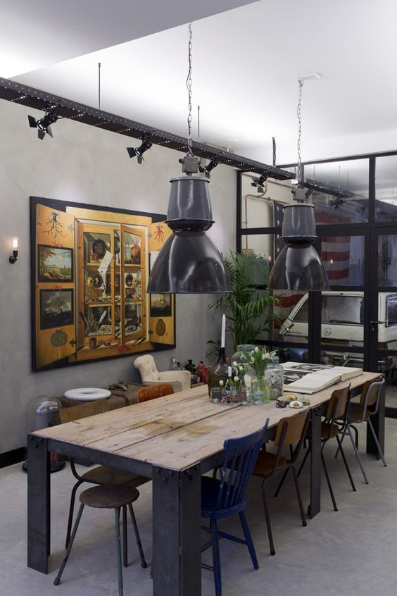 Industrial lamps hang over a custom table in a home built inside a restored commercial building dating from the 1950s in Amsterdam, Jan. 15, 2014. The unconventional living space hidden behind a steel roll-down door belongs to James van der Velden, an architect and interior designer who planned much of the decor as homage to the building's industrial past. (Andreas Meichsner/The New York Times)